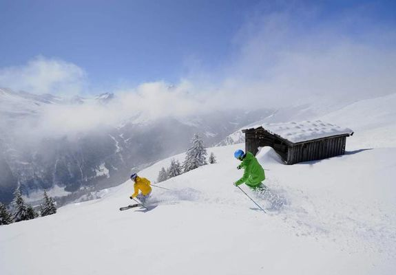 Two speedy skiers wend their way down the snow-covered side of the Arlberg